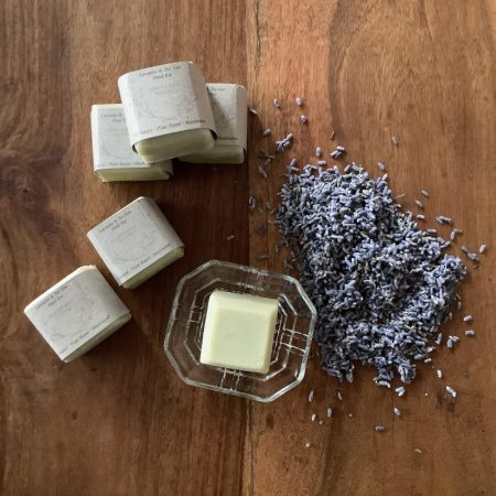 One of the specialty bars, a 4cm square hand washing bar on soap dish displayed with lavender petals.